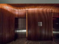 Light is used in slots next to the elevator doors. When the call button is pressed, light is used to signal the available elevator car. Pure Timber fabricated removable panels and recesses for the LED lighting